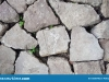 gray-huge-flat-uneven-stones-bricks-lie-ground-cementing-there-grass-deep-cracks-rocks-abstract-150307962