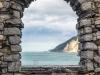 vista-mare-da-una-finestra-di-pietra-di-un-vecchio-rudere-muro-di-castello-di-portovenere-liguria-italia-pjc8yh